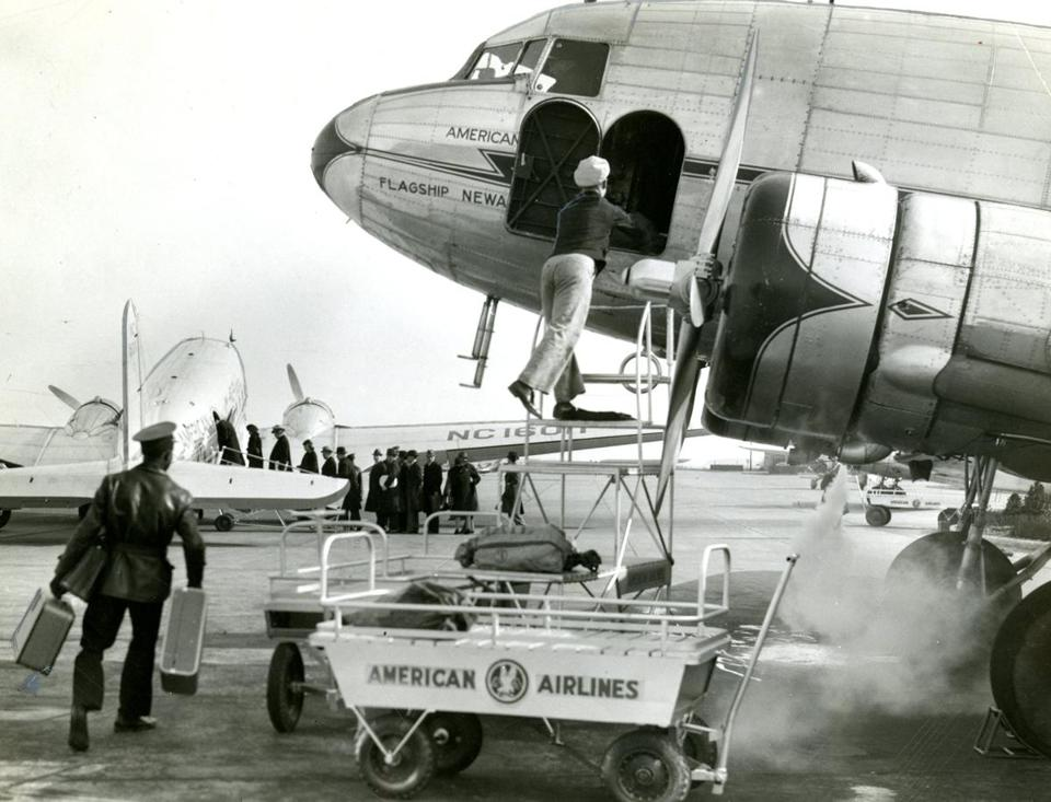 Feb. 19, 1940: A porter unloaded baggage from an incoming American Airlines flight. Passenger traffic over routes of American Airlines had set a new record for air traffic in January, when the flagships transported 45,939 passengers an increase of 83.5 percent over January 1939.